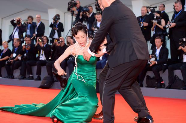 "A guest falls on the red carpet before the premiere of the movie ""The Light Between Oceans"" presented in competition at the 73rd Venice Film Festival on September 1, 2016 at Venice Lido. / AFP PHOTO / FILIPPO MONTEFORTEFILIPPO MONTEFORTE/AFP/Getty Images"