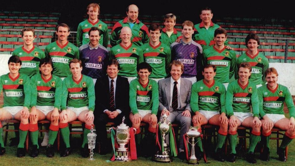 The Glentoran team of 87/88 are one of only three in the club's history to win both the Irish Cup (second right) and the league championship (second left) in the same season.