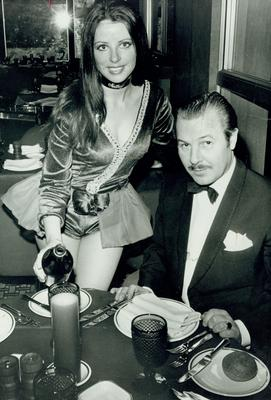 Harper Brown:Manager of the Europa Hotel, being served in the Penthouse Restaurant by one ot the 'Poppets', 20/12/1971