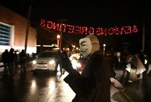 A demonstrator wears a Guy Fawkes mask as he protests the shooting death of 18-year-old Michael Brown on November 21, 2014 in Ferguson, Missouri. (Photo by Scott Olson/Getty Images)