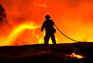 Firefighter Joe Darr douses flames of the Rocky fire along Highway 20 near Clearlake, California on August 2, 2015. Thousands of firefighters battled raging wildfires on August 2 in drought-parched California, where officials evacuated entire neighborhoods and closed miles of highway in the path of the inferno, which has claimed at least one life. AFP PHOTO / JOSH EDELSONJosh Edelson/AFP/Getty Images