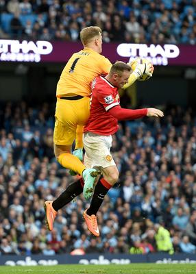 Manchester United's Wayne Rooney collides with Manchester City's Joe Hart during the Barclays Premier League match at the Etihad Stadium, Manchester. Martin Rickett/PA Wire.