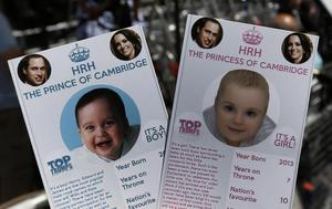Cards depicting the 'royal baby' either as a boy or a girl, specially made by a games company as a publicity stunt are pictured, backdropped by members of the media waiting across the St. Mary's Hospital exclusive Lindo Wing in London, Thursday, July 11, 2013. Media are preparing for royal-mania as Britain's Duchess of Cambridge plans to give birth to the new third-in-line to the throne in mid-July, at the Lindo Wing. Cameras from all over the world are set to be jostling outside for an exclusive first glimpse of Britain's Prince William and the Duchess of Cambridge's first child. (AP Photo/Lefteris Pitarakis)