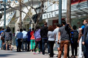 Customers wait in line to put a USD 1,000 deposit on the as yet unseen Tesla Model 3, outside the Tesla store on the Third Street Promenade in Santa Monica, California, on March 31, 2016.   / AFP PHOTO / ROBYN BECKROBYN BECK/AFP/Getty Images