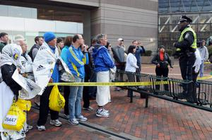 BOSTON, MA - APRIL 15:  Runners listen to directions from a Boston Police officer at the corner of Stuart Street and Dartmouth Street after two explosive devices detonated at the finish line of the 117th Boston Marathon on April 15, 2013 in Boston, Massachusetts. Two people are confirmed dead and at least 23 injured after two explosions went off near the finish line to the marathon.
