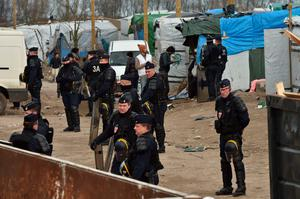 "Policemen stand next to shelters on February 29, 2016 in the ""jungle"" migrants and refugees camp in Calais, northern France as agents dismantle the southern half of the sprawling camp in the port town.  A French court on February 25 gave the green light to plans to evacuate hundreds of migrants, with many wanting to stay near the entrance to the Channel Tunnel, the gateway to their ultimate goal of Britain. AFP PHOTO / PHILIPPE HUGUENPHILIPPE HUGUEN/AFP/Getty Images"