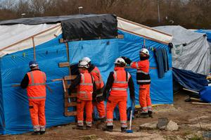 "Agents dismantle a shelter on February 29, 2016 in the ""jungle"" migrants and refugees camp in Calais, northern France.  A French court on February 25 gave the green light to plans to evacuate hundreds of migrants from the southern half of the sprawling camp in the port town, with many wanting to stay near the entrance to the Channel Tunnel, the gateway to their ultimate goal of Britain. AFP PHOTO / PHILIPPE HUGUENPHILIPPE HUGUEN/AFP/Getty Images"