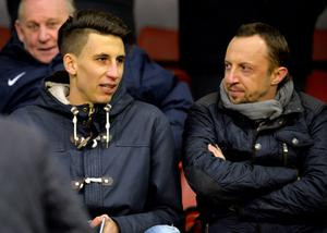 Liverpool's new signing Serbian Marko Grujic (L) talks during the English Premier League football match between Liverpool and Arsenal at Anfield stadium in Liverpool, north-west England on January 13, 2016. AFP PHOTO / PAUL ELLIS RESTRICTED TO EDITORIAL USE. NO USE WITH UNAUTHORIZED AUDIO, VIDEO, DATA, FIXTURE LISTS, CLUB/LEAGUE LOGOS OR 'LIVE' SERVICES. ONLINE IN-MATCH USE LIMITED TO 75 IMAGES, NO VIDEO EMULATION. NO USE IN BETTING, GAMES OR SINGLE CLUB/LEAGUE/PLAYER PUBLICATIONS.PAUL ELLIS/AFP/Getty Images