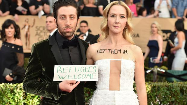 Simon Helberg, left, and Jocelyn Towne display protest signs against the U.S. policy of temporarily barring refugees and citizens of seven predominantly Muslim countries, at the 23rd annual Screen Actors Guild Awards at the Shrine Auditorium & Expo Hall on Sunday, Jan. 29, 2017, in Los Angeles. (Photo by Jordan Strauss/Invision/AP)