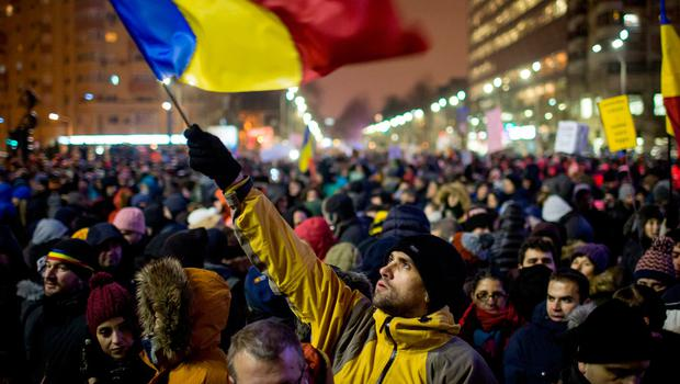 TOPSHOT - A man holds a Romanian national flag during a demonstration to protest against controversial decrees to pardon corrupt politicians and decriminalise other offences, on January 29, 2017 in Bucharest. Around 40,000 demonstrators took to the streets of Bucharest and other Romanian towns on January 29, 2017. / AFP PHOTO / ANDREI PUNGOVSCHIANDREI PUNGOVSCHI/AFP/Getty Images