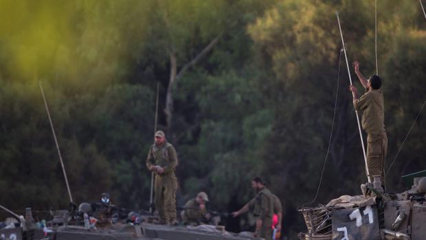 Israeli soldiers work on their tanks near the Israel Gaza Border, early Tuesday, July 15, 2014. The Israeli Cabinet has accepted an Egyptian proposal for a cease-fire to end a week of conflict with Hamas militants in the Gaza Strip that has killed 185 Palestinians and exposed millions of Israelis to Hamas rocket fire. No Israelis have been killed as a result of Hamas rocket launches. A senior Hamas official says the Palestinian militant group rejects an Egyptian proposal for a cease-fire with Israel. (AP Photo/Ariel Schalit)