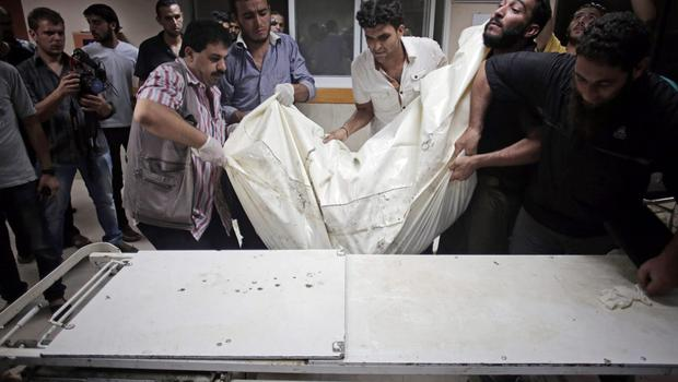 Palestinian hospital workers carry a body of one of the six members of the Gharabli family who were killed in an Israeli strike, at the Shifa hospital, in Gaza City, Monday, July 21, 2014. (AP Photo/Khalil Hamra)