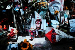 """NEW YORK, NY - JANUARY 11:  Flowers, candles and pictures sit at a memorial outside of the late musician and performer David Bowie's apartment that he shared with his wife on January 11, 2016 in New York City. A growing memorial sits outside of the residence in lower Manhattan following news that Bowie died over the weekend following 18 month battle with cancer. Bowie was 69 and had just released his 25th studio album, """"Blackstar,"""" to strong reviews on January 8. (Photo by Spencer Platt/Getty Images)"""