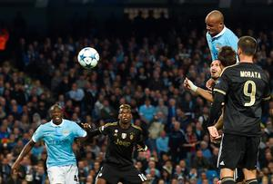 Juventus' defender from Italy Giorgio Chiellini (3R) heads the ball by Manchester City's Belgian defender Vincent Kompany (R) to score an own goal during a UEFA Champions League group stage football match between Manchester City and Juventus at the Etihad stadium in Manchester, north-west England on September 15, 2015.  AFP PHOTO / PAUL ELLISPAUL ELLIS/AFP/Getty Images