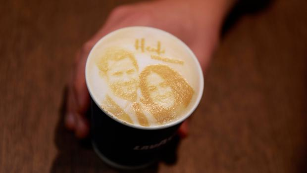 A barrista poses with a  'Megharryccino', a Royal Wedding-themed coffee decorated with the faces of Britain's Prince Harryand Meghan Markle, in a coffee shop in Windsor  )AFP PHOTO / Odd ANDERSENODD ANDERSEN/AFP/Getty Images)