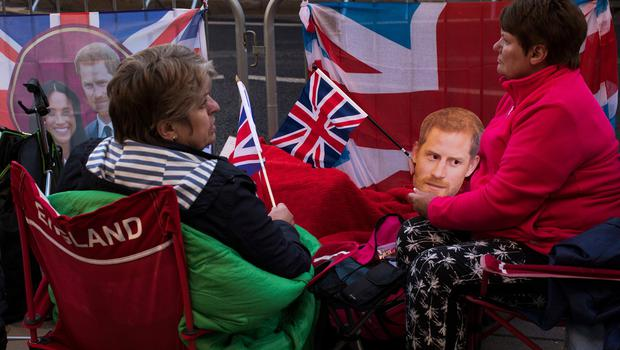 Fans spend the night in front of Windsor castle, England, Friday, May 18, 2018. Preparations continue in Windsor ahead of the royal wedding of Britain's Prince Harry and Meghan Markle Saturday May 19. (AP Photo/Emilio Morenatti)