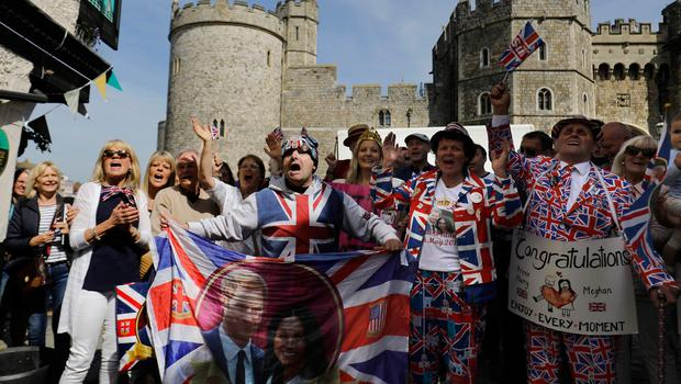 Royal fans including John Laughry (C) and Terry Hutt (R) sing for the television in Windsor on May 18, 2018, the day before the Royal wedding.  Britain's Prince Harry and US actress Meghan Markle will marry on May 19 at St George's Chapel in Windsor Castle. / AFP PHOTO / Tolga AKMENTOLGA AKMEN/AFP/Getty Images