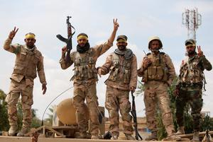 Shiite fighters from the Popular Mobilisation units flash the sign for victory in Tikrit on April 1, 2015, a day after the Iraqi Prime Minister Haider al-Abadi declared victory in the weeks-long battle to retake the northern Iraqi city from the Islamic State (IS) group. Iraqi forces battled the last jihadists in Tikrit to seal a victory the government described as a milestone in efforts to rid the country of the jihadist group. AFP/Getty Images