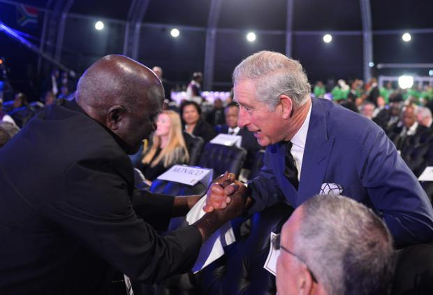 Britain's Prince Charles, right, is greeted by another mourner as he arrives for the funeral service for former South African president Nelson Mandela in Qunu, South Africa, Sunday, December 15, 2013. (AP Photo/Odd Andersen, Pool)