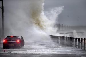 A car drives along Seaview road as waves crash over on December 9, 2014 in Saltcoats ,Scotland. The Met Office has issued a yellow weather warning for the next forty eight hours as high winds start to build ahead of an Atlantic storm due tomorrow.  (Photo by Jeff J Mitchell/Getty Images)