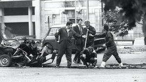 Police forensic officers working on the remains of the IRA car which housed yesterday's Hyde Park car bomb. Detectives are trying to trace the owner of the car, which contained the nail bomb. It was a blue Morris saloon, registration LMD 657P.
