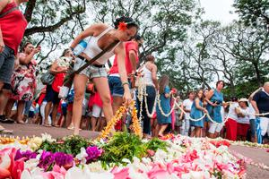 People lay flowers and garlands as they gather at the Pouvanaa a Oopa Monument, in Papeete in front of the Assembly of French Polynesia, on November 15, 2015, to pay tribute to the victims of attacks in the French capital Paris on November 13, in which over 130 people died and more than 350 were injured. Hundreds of meters of flower garlands were made for the remembrance and a minute of silence was held. AFP PHOTO / GREGORY BOISYYGREGORY BOISSY/AFP/Getty Images