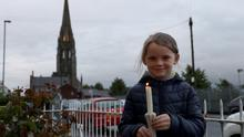 People in Derry lit candles in memory of John Hume. Pictured is Aoife Bryce. Photo Pacemaker Press.