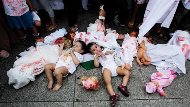 Two babies areplaced between dolls covered with red paint during a demonstration, most of them women and children, against Israel's military offensive in Gaza, Tuesday, July 22, 2014, in Berlin, Germany. Several hundred pro-Palestinian protesters demanded a halt to military action in Gaza. (AP Photo/Markus Schreiber)