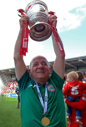 Hands on the prize: Tommy Breslin lifts the Gibson Cup after Cliftonville defended the trophy for the first time in the club's history