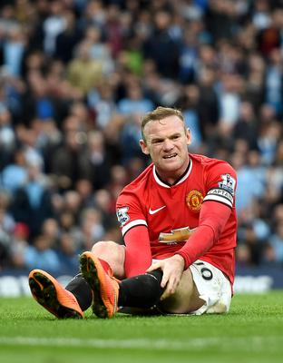 Manchester United's Wayne Rooney holds his leg after colliding with Manchester City's Joe Hart during the Barclays Premier League match at the Etihad Stadium, Manchester. Martin Rickett/PA Wire.