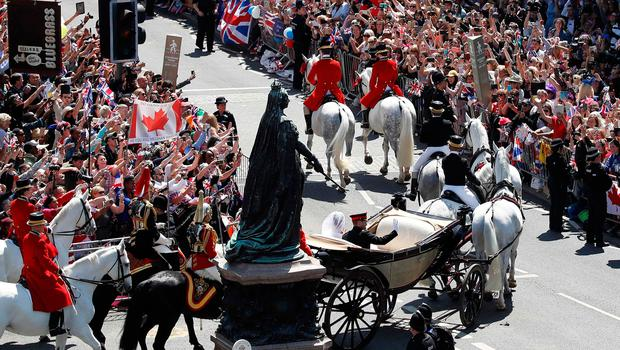 Well-wishers lining the streets wave and cheer as Britain's Prince Harry, Duke of Sussex and his wife Meghan, Duchess of Sussex pass riding in the Ascot Landau Carriage during their carriage procession taking the turn from Castle Hill onto the High Street outside Windsor Castle in Windsor, on May 19, 2018 after their wedding ceremony.  / AFP PHOTO / POOL AND AFP PHOTO / Odd ANDERSENODD ANDERSEN/AFP/Getty Images