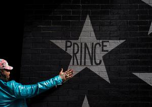 MINNEAPOLIS, MN - APRIL 21: A woman touches the Prince star on the wall outside the First Avenue nightclub on April 21, 2016 in Minneapolis, Minnesota. Prince died earlier today at his Paisley Park compound at the age of 57. (Photo by Stephen Maturen/Getty Images)
