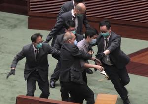 Ted Hui struggles with security personnel (AP)