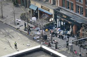 One of the blast sites on Boylston Street near the finish line of the 2013 Boston Marathon is investigated and guarded by police in the wake of two blasts in Boston Monday, April 15, 2013. (AP Photo/Elise Amendola)