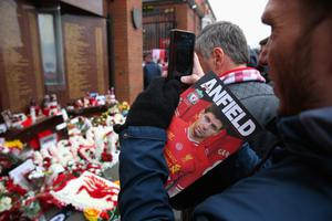 LIVERPOOL, ENGLAND - APRIL 13:  A fan takes a photo of floral tributes laid in memory of the victims of the Hillsborough disaster, on the 25th anniversary of the tragedy prior to the Barclays Premier League match between Liverpool and Manchester City at Anfield on April 13, 2014 in Liverpool, England.  (Photo by Alex Livesey/Getty Images)