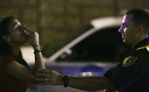 A US police officer helps steady a woman take a sobriety test at a traffic checkpoint (Photo by Joe Raedle/Getty Images)