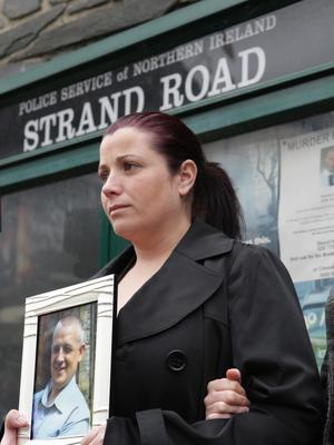 Lorna Brady holds a photograph of her late brother, John Brady, during the protest outside Strand Road PSNI Station. Photo Lorcan Doherty / Presseye.com