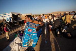 A man carries a box after crossing the border from Syria into Turkey on October 1 , 2014 near Suruc, Turkey. Kurdish troops are engaged in a battle against fighters of the Islamic State (IS, also called ISIS and ISIL) to defend the strategic nearby Kurdish border town of Kobani (also called Ayn Al-Arab), which ISIS has surrounded on three sides. The Turkish Parliament is due to vote on a measure on October 2, which would allow Turkish ground forces to enter Syria, creating a buffer zone to protect fleeing refugees from the ISIS advance.  (Photo by Carsten Koall/Getty Images)