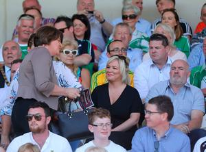 DUP Leader Arlene Foster (left) walks past Sinn Fein Vice President Michelle O'Neill (centre) at the Ulster final between Fermanagh and Donegal in Clones, Co Monaghan, Ireland. PRESS ASSOCIATION Photo. Picture date: Sunday June 24, 2018. Mrs Foster's attendance at a game synonymous with the nationalist tradition marks another symbolic milestone in cross-community engagement in the region. See PA story ULSTER Final. Photo credit should read: Niall Carson/PA Wire