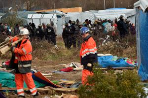 "Agents dismantle a shelter as anti-riot policemen stand nearby on February 29, 2016 in the ""jungle"" migrants and refugees camp in Calais, northern France.  A French court on February 25 gave the green light to plans to evacuate hundreds of migrants from the southern half of the sprawling camp in the port town, with many wanting to stay near the entrance to the Channel Tunnel, the gateway to their ultimate goal of Britain. AFP PHOTO / PHILIPPE HUGUENPHILIPPE HUGUEN/AFP/Getty Images"