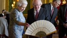 Queen Elizabeth II shows Irish President Michael D Higgins Irish related items from the Royal Collection, in the Green Drawing Room at Windsor Castle on April 8, 2014 in Windsor, England.  (Photo by Justin Tallis - WPA Pool/Getty Images)