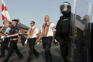 Press Eye - Belfast -  Friday 12th July 2013   The outward leg of the north Belfast feeder parade passes the Nationalist Ardoyne shops in north Belfast where Orangemen and bands marched past the Nationalist residents from the Greater Ardoyne Residents' Collective (GARC) held a small protest in the area, amid a heavy police presence. Thousands of Orangemen are taking part in the annual Twelfth of July parades across Northern Ireland. Picture by Kelvin Boyes / Press Eye.