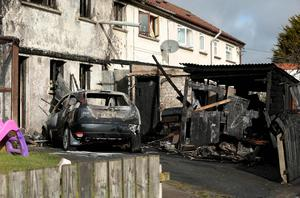 Three people have escaped injury after a car was set on fire and pushed up against their home in Richhill, Co Armagh. Picture by Kelvin Boyes / Press Eye.