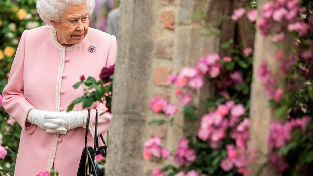 Britain's Queen Elizabeth II looks at a display of roses on the Peter Beale stand as she visits the 2018 Chelsea Flower Show in London on May 21, 2018. The Chelsea flower show, held annually in the grounds of the Royal Hospital Chelsea, opens to the public on May 22.  / AFP PHOTO / POOL / RICHARD POHLERICHARD POHLE/AFP/Getty Images