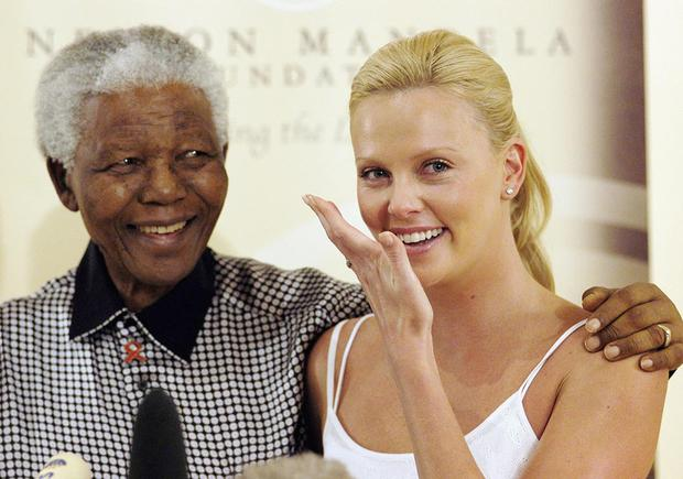 JOHANNESBURG, SOUTH AFRICA - MARCH 11:  Oscar winning acress Charlize Theron wipes away tears as she meets former South African President Nelson Mandela at Mandela House following her Academy Awards success, on March 11, 2004 in Johannesburg, South Africa. (Photo by Naashon Zalk/Getty Images) *** Local Caption *** Charlize Theron;Nelson Mandela