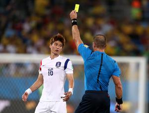 CUIABA, BRAZIL - JUNE 17:  Ki Sung-Yueng of South Korea is shown a yellow card by referee Nestor Pitana during the 2014 FIFA World Cup Brazil Group H match between Russia and South Korea at Arena Pantanal on June 17, 2014 in Cuiaba, Brazil.  (Photo by Warren Little/Getty Images)