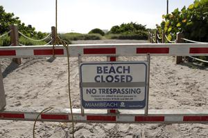 A sign at a closed entrance in the South Beach neighbourhood of Miami Beach, Florida (Lynne Sladky/AP)