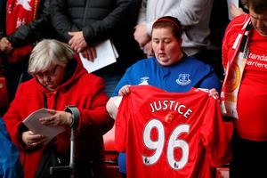 LIVERPOOL, ENGLAND - APRIL 15:  An Everton FC supporter holds up a Liverpool FC supporters shirt during a memorial service to mark the 27th anniversary of the Hillsborough disaster, at Anfield stadium on April 15, 2016 in Liverpool, England. Thousands of fans, friends and relatives took part in the final Anfield memorial service for the 96 victims of the Hillsborough disaster. Earlier this year relatives of the victims agreed that this year's service would be the last. Bells across the City of Liverpool rung out during a one minute silence in memory of the 96 Liverpool supporters who lost their lives during a crush at an FA Cup semi-final match against Nottingham Forest at the Hillsborough football ground in Sheffield, South Yorkshire in 1989.  (Photo by Christopher Furlong/Getty Images)