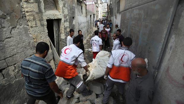 Palestinian medics carry a dead body found under the rubble of a home destroyed by an Israeli strike in the Shajaiyeh neighborhood of Gaza City, northern Gaza Strip, Sunday, July 20, 2014. (AP Photo/Hatem Moussa)