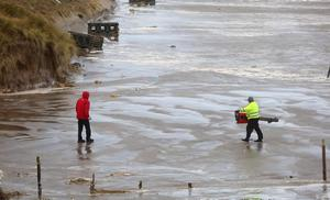 National Trust members clearing damage of the beach at Portstewart Strand